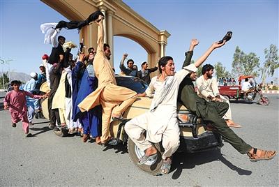 阿富汗塔利班武装人员16日出现在喀布尔和其他多座大城市,与民众和安全部队人员互动。图/视觉中国