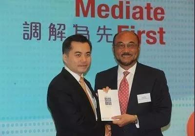 """律政司在2009年5月展开""""调解为先""""承诺书运动。图为时任律政司司长黄仁龙(左)向商界简介""""调解为先""""承诺书。"""