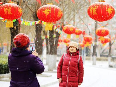北京国际雕塑公园内游人雪中赏红灯