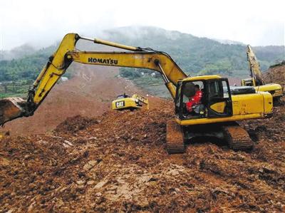 昨日,中国安能第一工程局救援人员在滑坡现场利用重型机械开展搜救。图/IC photo