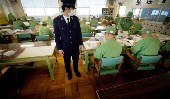 身着统一囚服的老年囚犯在看管下做手工。