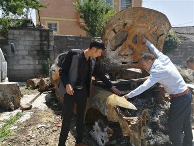 曾芝才(左)查看被烧毁的汽车