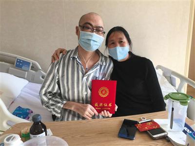 医院病房里,李真和母亲手持证书合影留念。受访者供图
