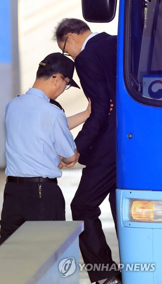 15日,李明博在狱警搀扶下走下囚车