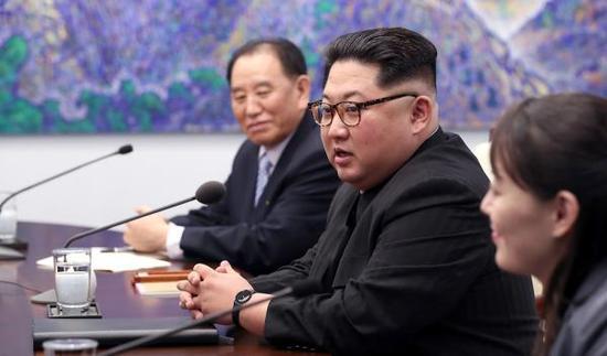 """朝鲜最高领导人金正恩身穿富有朝鲜特色的黑色""""人民装"""",戴着一副富有时尚气息的豹纹眼镜。"""