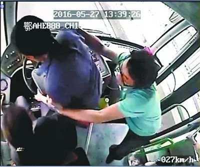 公交610路车上,男乘客吴烨(右)和司机(左)制止抢夺方向盘的女乘客(中)(视频截图)