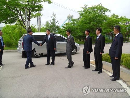 6月8日,在韩朝交流合作协议事务所前,韩朝共同联络事务所韩方考察团一行同朝方人士握手示意。(图片来源:韩联社)