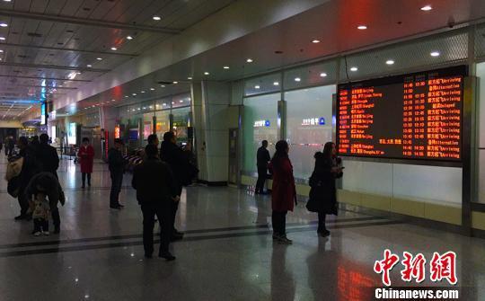 機場旅客看大屏幕瞭解航班信息。 郭一彤 攝