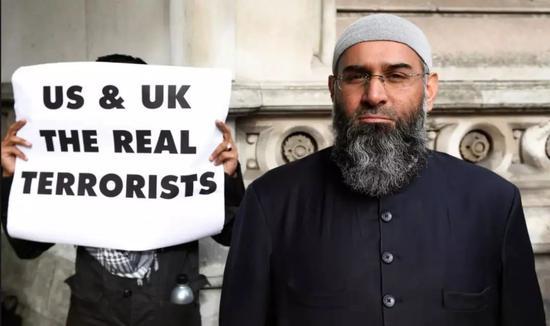 """安杰姆·乔杜里照片,旁边英文写着""""英美是真正的恐怖分子"""",图自《卫报》"""