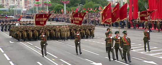 """穿苏联红军军服参加阅兵的方队,前方打着四个参加""""巴格拉季昂""""的红军方面军的军旗:波罗的海第一方面军,白俄罗斯第一方面军,白俄罗斯第二方面军,白俄罗斯第三方面军。"""