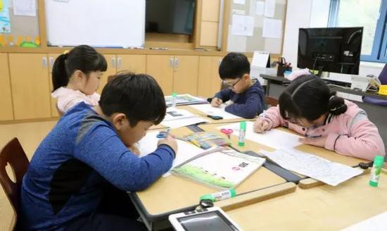 4月24日,学生在韩国大成洞村大成洞小学画画。 新华社记者李鹏摄