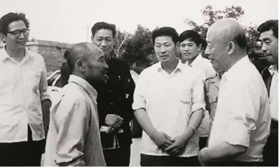 林乎加(前右)在调研期间与当地农民交流