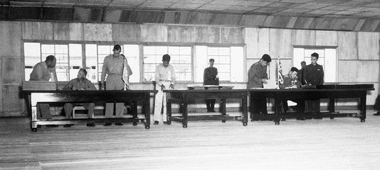 2018-08-16,《朝鲜停战协定》签署现场,左侧坐者为联合国军代表团首席代表、美国陆军中将威廉·凯·海立胜,右侧坐者为朝鲜人民军与中国人民志愿军代表团首席代表、朝鲜人民军大将南日。