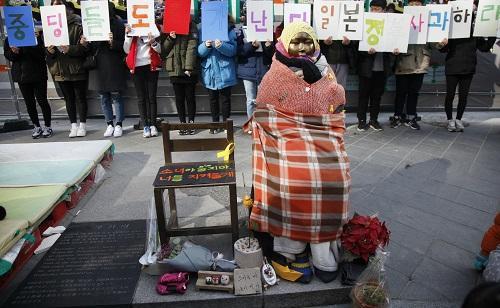 """資料圖片:2017年1月11日,在韓國首都首爾,學生們手舉標語與""""慰安婦""""少女像合影。新華社記者 姚琪琳 攝"""