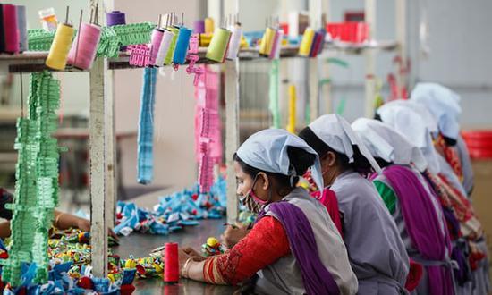 孟加拉国工人在达卡郊区的一家服装厂工作 《卫报》图