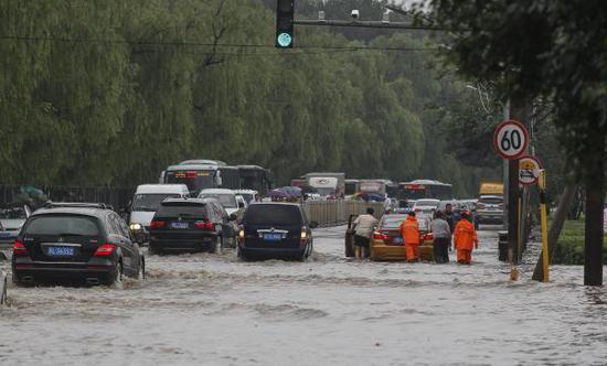 2018年7月9日下午,北京市海淀区突降暴雨,黑龙潭路附近积水严重,致多辆汽车抛锚。 视觉中国 图