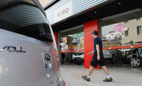资料图:一名男子从巴西里约热内卢的一家起亚汽车展示厅门前走过。 (新华社)