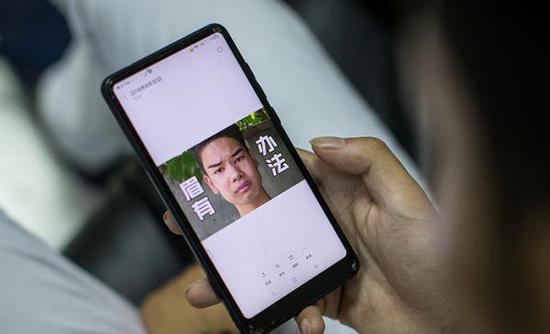 8月30日,吴正强在看网友给他做的各种表情包,并一一保存了下来。视觉中国 图
