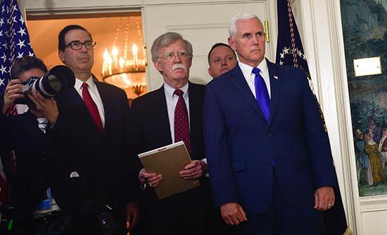 美国国家安全顾问博尔顿(中)等旁观特朗普宣布美国将退出伊朗核问题全面协议的讲话。视觉中国 图