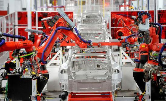 在美国加利福尼亚州弗里蒙特的特斯拉工厂,机器人手臂组装汽车零件。(新华社/路透)