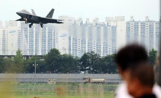 """5月16日,一架美军F-22""""猛禽""""战斗机飞过韩国光州一栋公寓楼。 新华社 图"""