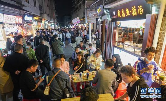 3月28日,人们在武汉市闻名的小吃街户部巷休闲消耗。新华社记者 程敏 摄