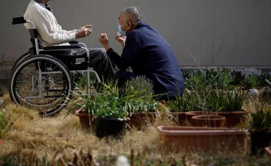 一名92岁的男囚犯在护工的陪同下坐轮椅锻炼。