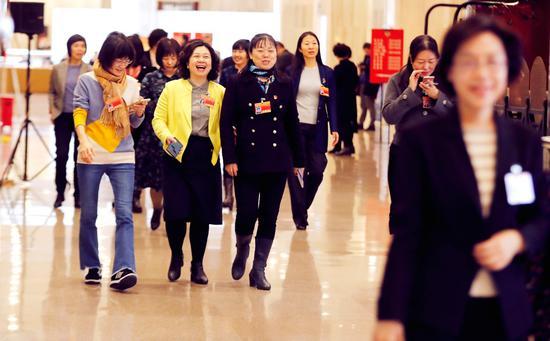 在市政协十三届三次会议委员驻地通往小组会场的走廊上,委员们边走边议,讨论各自关注的话题。