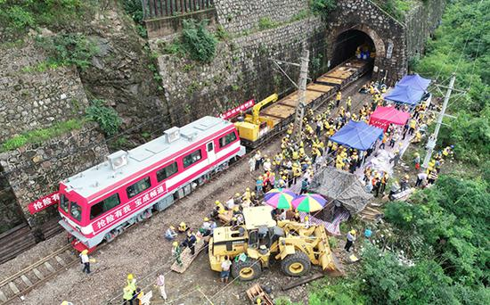 7月14日,抢险人员在宝成铁道陕西略阳段王家沱至乐素河区间举行铁道抢通处事(无人机拍摄)。