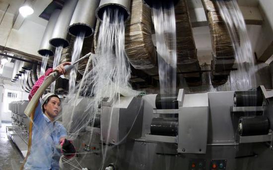 资料图:工人将烘干后的塑料碎片加工成丝状。新华社发