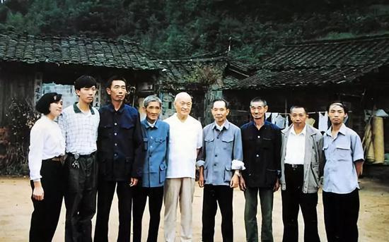 1986年5月,項南(中)在祖屋前與連城縣朋口鄉文地村的鄉親們在一起。
