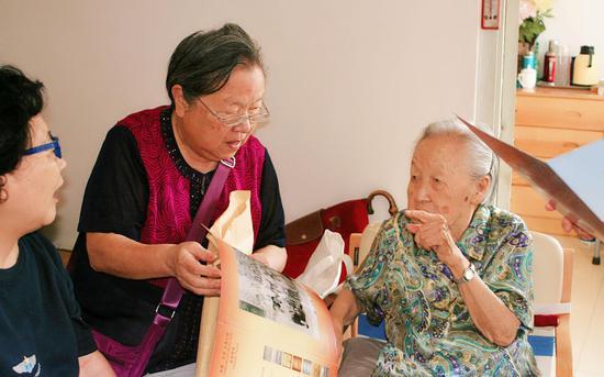 老人们看着老照片话当年往事。受访者供图