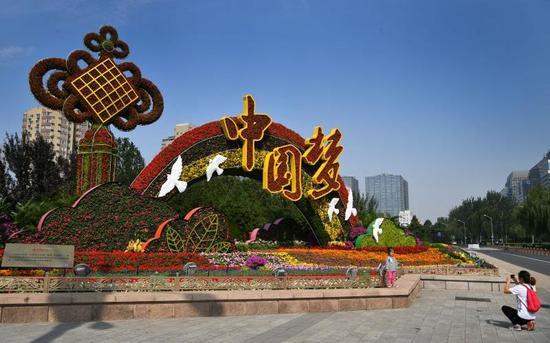 """市民在复兴门东北角的""""美好明天""""花坛前拍照留念。摄影/新京报记者 吴江"""