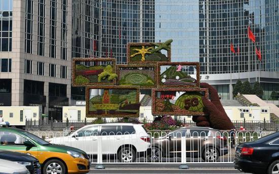 """东方广场的""""繁荣发展""""花坛,展现了交通、水利、能源、通信、科技、体育等领域取得的巨大成就。摄影/新京报记者 吴江"""
