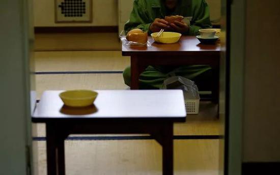 一名老年囚犯正在享用午餐。