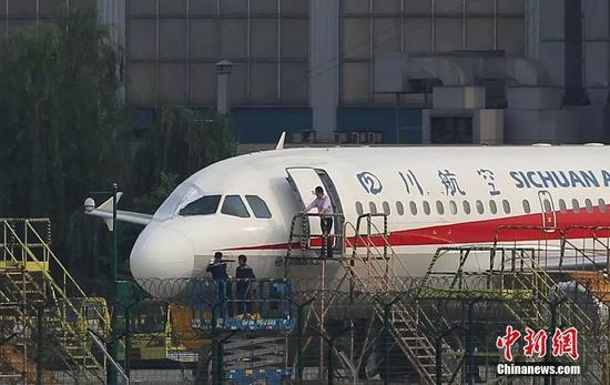 5月14日17时,成都机务人员正在对注册号为B-6419的空客A319客机进行检查,破损的右侧风挡玻璃处已经被临时遮挡。中新社发 汪龙华 摄