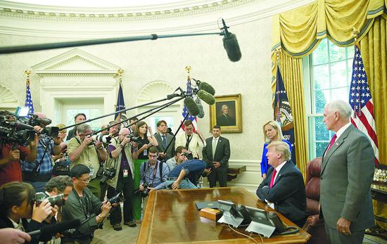"""图片说明: 当地时间20日,特朗普在白宫签署行政命令,暂停了此前备受争议的""""骨肉分离""""政策。"""