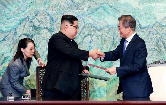 4月27日,朝鲜国务委员会委员长金正恩(中)与韩国总统文在寅在板门店交换签署的《为实现半岛和平、繁荣和统一的板门店宣言》。左为金与正。 图/韩朝首脑会晤媒体报道团