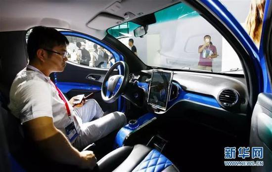 新能源车展上,参观者正在体验一款电动车。(新华社)