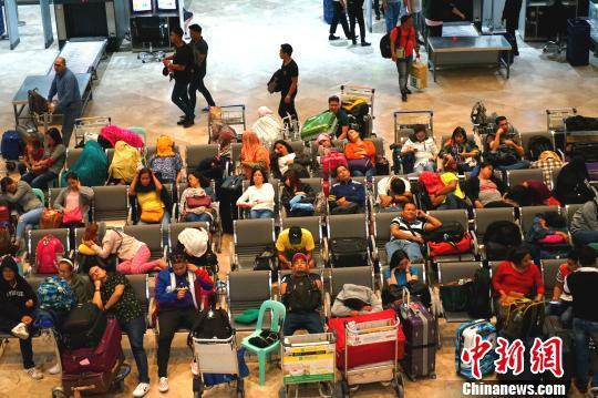 17日夜,大量滞留旅客在马尼拉国际机场航站楼休息等候。 关向东 摄