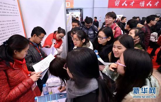 资料图:学生在招聘会上咨询信息。新华社记者 刘潇 摄