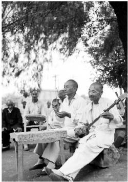 1953年7月21日,辽宁抚顺市工人养老院。70岁的张静明在院内树荫下弹三弦,60岁的李秀峰打鼓说书。赵眏摄 (本报资料照片)