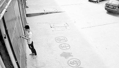 摩托车店门口的监控画面:14时32分,年轻人从地上捡起一个细长物体,用它摆弄门锁。