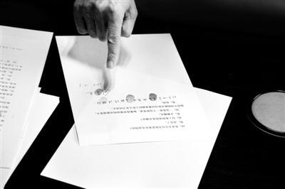 图为刘喜杰在谈话笔录上按手印。
