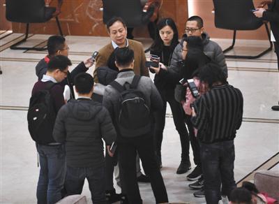 记者围住一名全国政协委员采访。