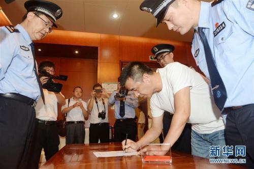 """资料图:2017年9月25日,在杭州萧山机场,""""百名红通人员""""徐雪伟在逮捕证上签字。新华社发 张立伟 摄 图片来源:新华网"""