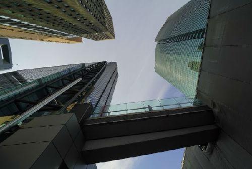 资料图:在日本东京的商业区,行人走在天桥上。(新华/美联)