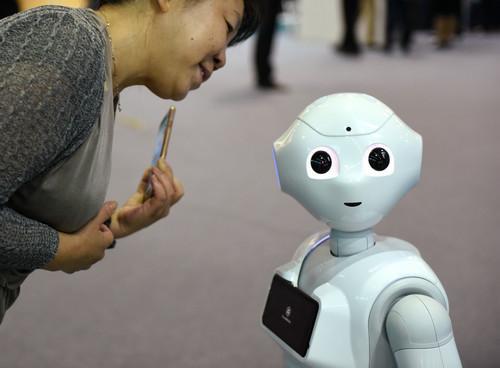 资料图片:在2017年全国大众创业万众创新活动周北京会场主题展上,一款智能机器人与参观者互动。新华社记者 张晨霖 摄