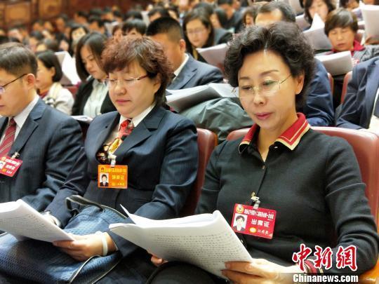 与会人员认真阅读政府工作报告。 赵桂华 摄