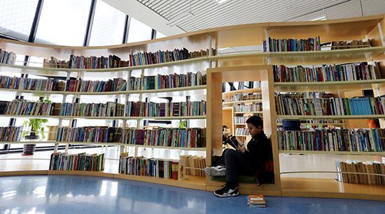 图为一名小读者在图书馆里津津有味地享受阅读乐趣。视觉中国 图